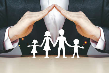 Asian insurance businessmen use their hands to protect the white paper families who are enjoying the idea of helping guide and maintain business services at home.