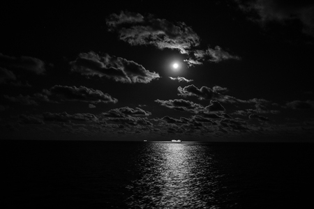 Cruise ship in the night with the moon and clouds