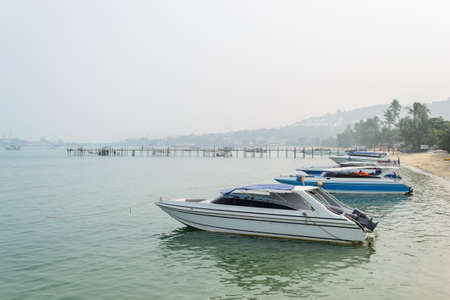furled: Speed Boats moored on tropical sea in Samui Island,Thailand with foggy sky.