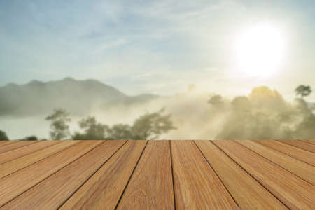 table top: Wood table top on blurred mountain at morning sunrise background for presentation product. Stock Photo