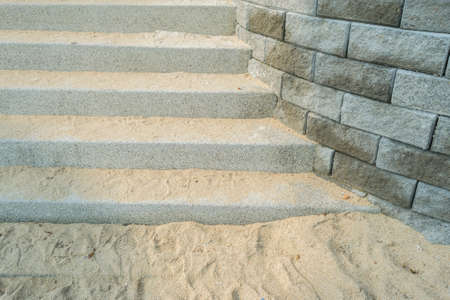 stair well: Concrete stairs with rocks beside and sand beach Stock Photo