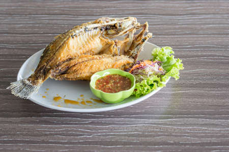 fried fish and seafood sauce on wood table background, Thai food.