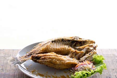 fried fish and seafood sauce on wood table and white background, Thai food. 版權商用圖片