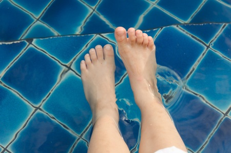 little girls legs soaking in the pool photo