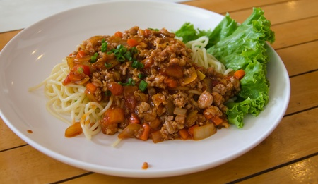Spaghetti with tomato sauce and topped with ground pork and vegetables. photo
