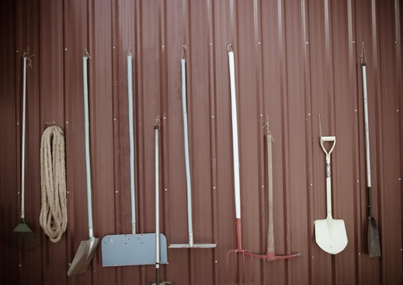 Gardening tools hanging on the wall. A vintage. photo