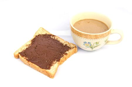 Slice of bread with chocolate cream and coffee mug photo