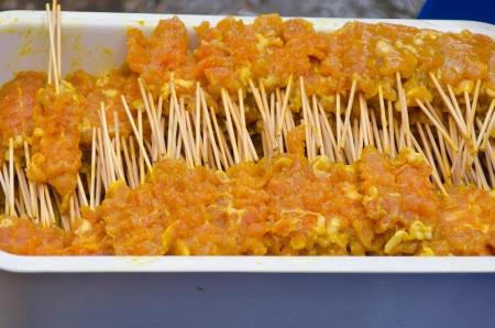 Many pork satay sticks. Placed in a rectangular tray. photo