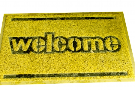 Doormat yellow on a white background. The word welcome.