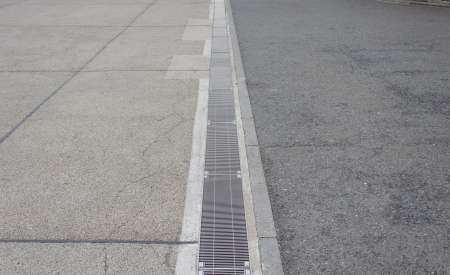 Sewer grate that drains water from a parking lot. Stock Photo