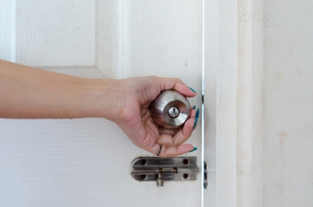 Hand on a handle wooden door to open or close it  Stock Photo