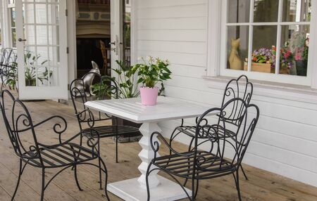 Black iron chairs on the front porch.