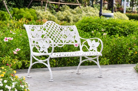 White iron chair in garden with trees.