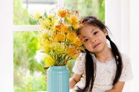 Girl sitting. Picture with flowers in a vase.