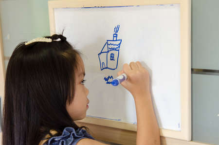 Child drawing on a white board at home.