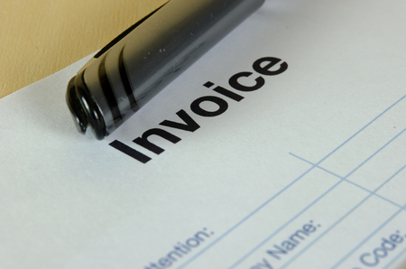 The invoices bill black pen on the table.