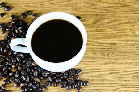 Close up of coffee cup with beans Stock Photo