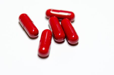 The medicine red capsules on white background.