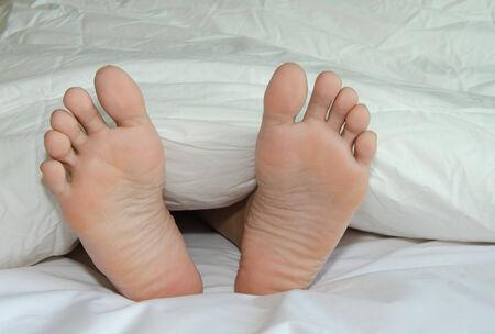 Fuß ruht auf einem Bett mit einem weißen Tuch bedeckt. Standard-Bild