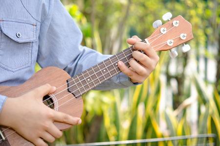 O menino que joga o ukulele no jardim Banco de Imagens