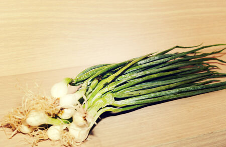 spring onions placed on a wooden brown. photo