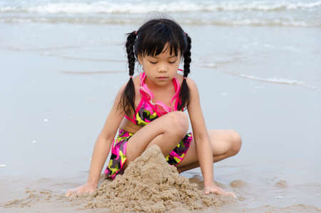 Girl playing in sand at the beach.