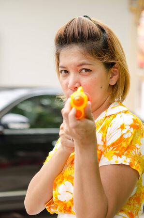 watergun: Asian women playing Songkran water gun.