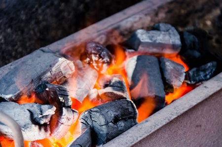 flame over burning wood-burning coals close up photo