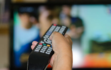Hand holding TV remote control with a television in the background. Standard-Bild