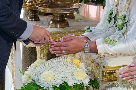 hand of a bride receiving holy water from elders in thai culture wedding ceremony photo