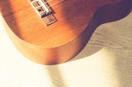 bluegrass: Vintage ukulele on wooden background.