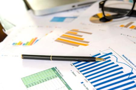 datos personales: Tablas financieras y gr?ficos en papel sobre la mesa Foto de archivo