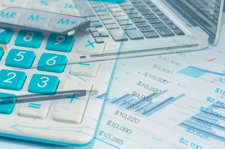 a calculator is on a balance sheet numbers are statistics. Stock Photo
