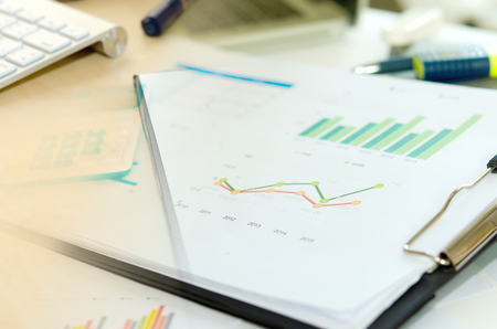 graph report: Financial paper charts and graphs on the table. Stock Photo