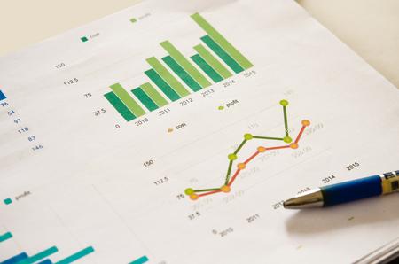 財務グラフ分析とペン。