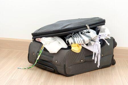 open suitcase: Open suitcase on floor in room.