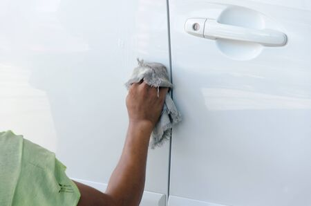 wiping: hand wiping water on white car Stock Photo