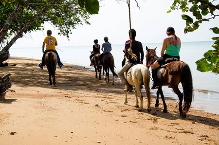 THAILAND, KARBI, FEBRUARY 24 2016.Tourists riding rented horses along the Ao Nang  beach Krabi  ,Thailand on February 24,2016