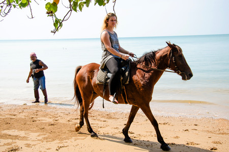 rented: THAILAND, KARBI, FEBRUARY 24 2016.Tourists riding rented horses along the Ao Nang  beach Krabi  ,Thailand on February 24,2016