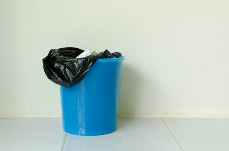 trash can with a plastic bag inside indoor
