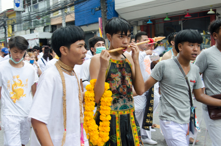 joins: PHUKET , THAILAND - OCT 6, 2016: Unidentified  Taoist devotee joins a procession of the Phuket Vegetarian Festival. The event is famous for its spirit mediums who undergo ritual mutilation and piercing.