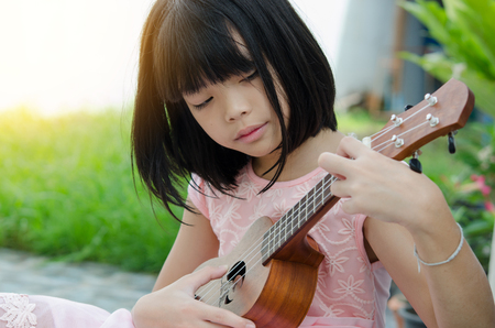 thai musical instrument: A little girl playing ukulele in the garden. Stock Photo