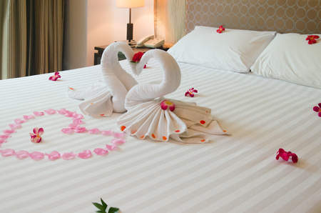 Interior bedroom Swan towel And orchid flowers on the bed. The hotel rooms are romantic for couples.