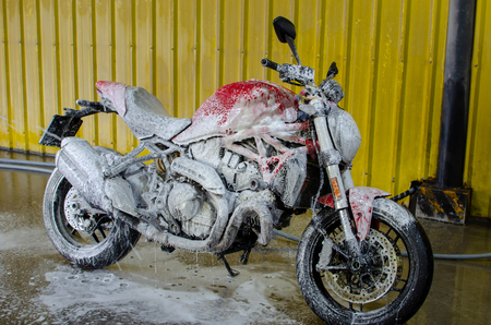 Red motorcycle washed with foam. Stockfoto