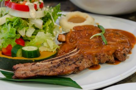 Pork steak and vegetable salad in a plate