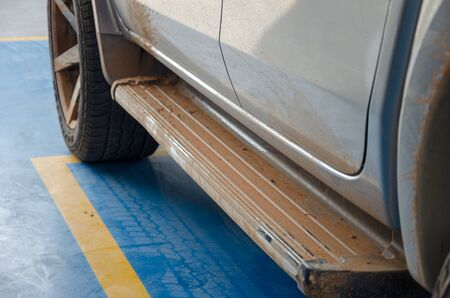 Dirty on the side of the silver car. Soil stains on the stairs of the pickup truck