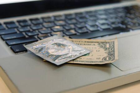 Condoms, dollar banks and notebooks. Buy sex services online Banco de Imagens