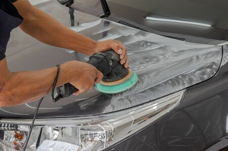 Man working for polishing, coating cars. polishing of the car will help eliminate contaminants on the surface of the car.Waxing the car surface will cause shine after polishing the car.