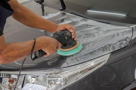 Mann, der für das Polieren und Beschichten von Autos arbeitet. Das Polieren des Autos hilft dabei, Verunreinigungen auf der Oberfläche des Autos zu entfernen. Das Wachsen der Autooberfläche führt nach dem Polieren des Autos zu Glanz. Standard-Bild