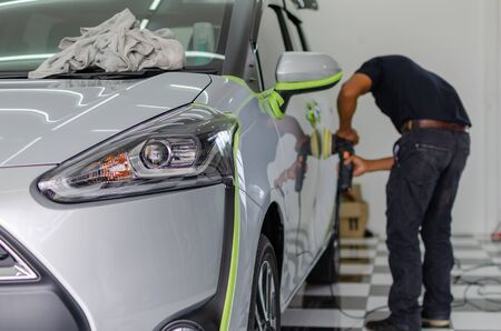 Man working for polishing, coating cars. polishing of the car will help eliminate contaminants on the surface of the car.Waxing the car surface will cause shine after polishing the car. Focus on the car headlights
